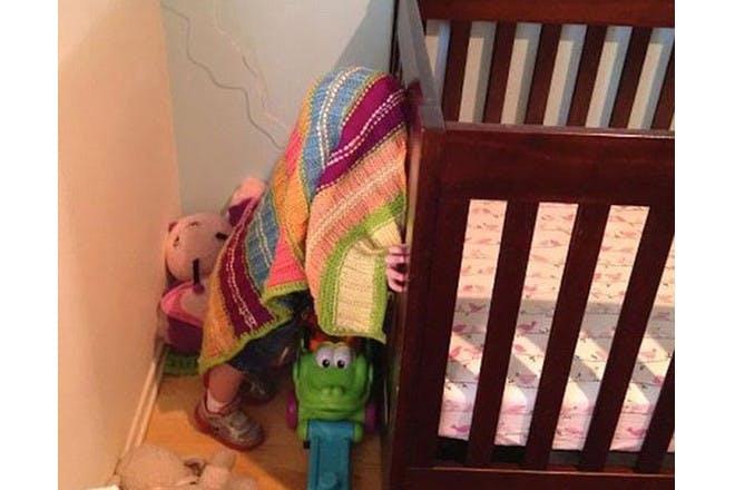 child hiding under blanket