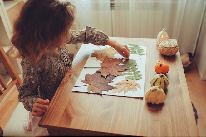 Little girl sticking autumn leaves onto paper