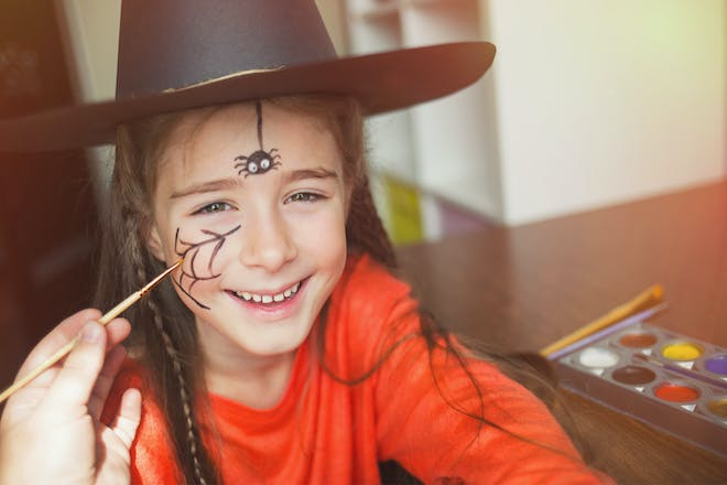 Girl in witch costume with spider face paint for Halloween
