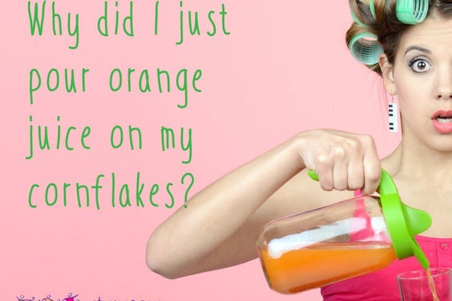 woman with rollers pouring orange juice looking frazzled