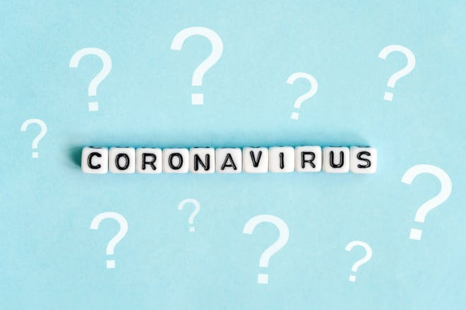 Coronavirus written on beads on pale blue background surrounded by question marks