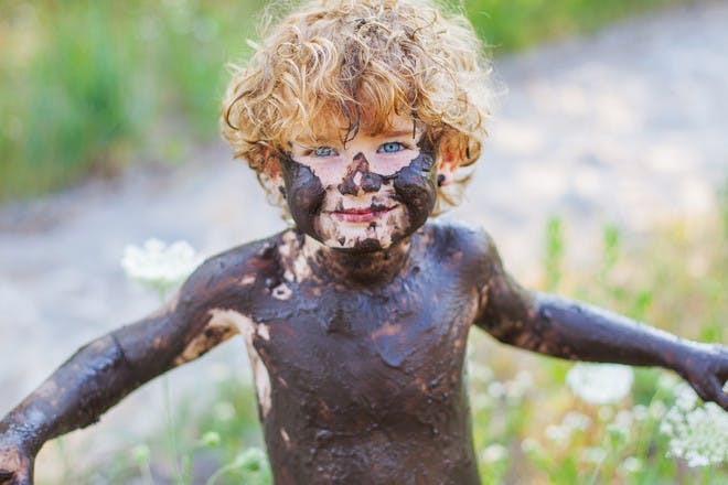 Little boy covered in mud