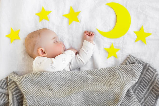 Sleeping baby surrounded by moon and stars