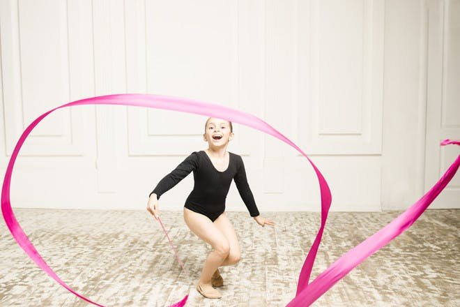 girl in gymnastics class with ribbon