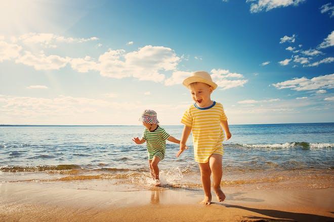 Young boys running on sunny beach