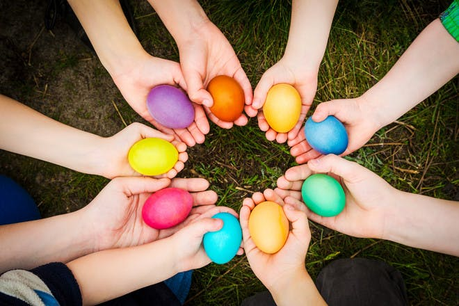 childrens hands all holding different coloured painted easter eggs