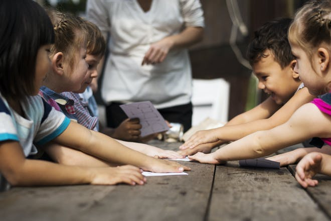 Young children playing a card game with word cards