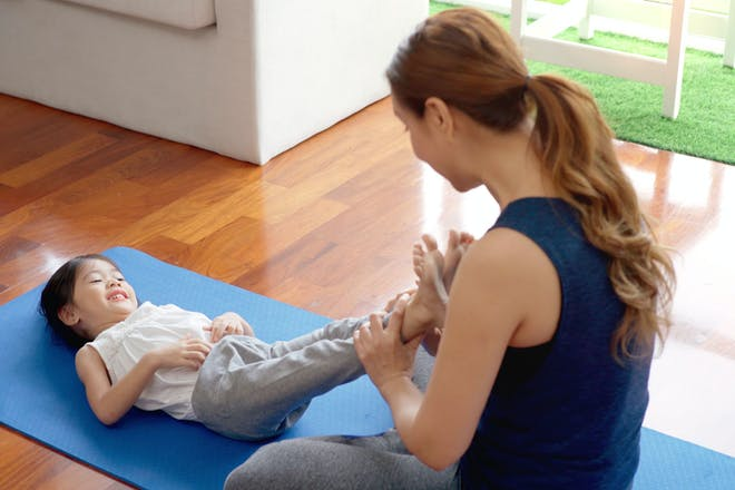 Mum doing yoga with girl on mat on floor