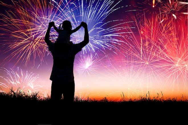 Silhouette of person watching fireworks with child on shoulder