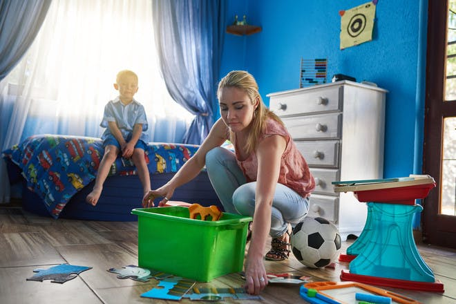 Mum cleaning kids' bedroom while boy watches