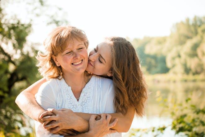 Older mum being hugged by daughter
