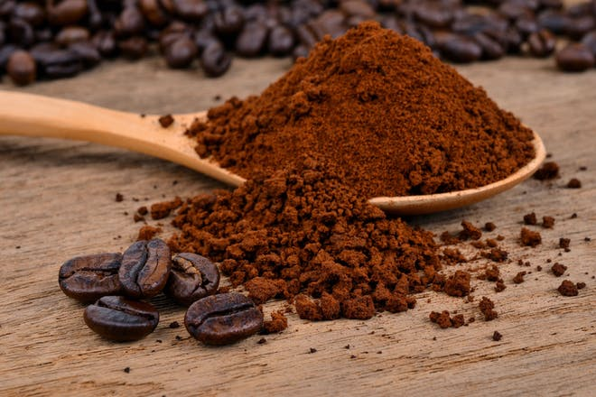 Coffee powder on wooden spoon with coffee beans