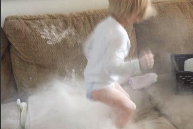 child jumping on sofa with powder everywhere