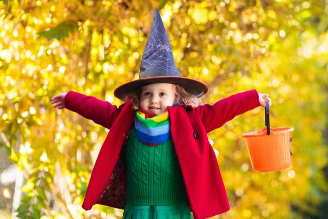 Little girl dressed in witch costume for Halloween stands with arms outstretched while holding orange pumpkin bucket