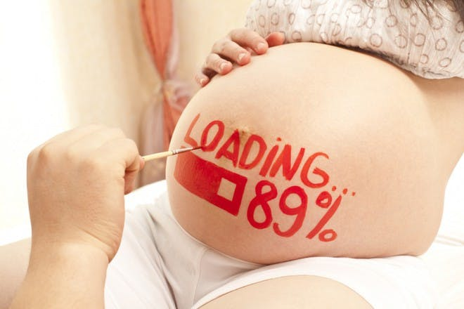 hand painting loading sign on pregnant belly