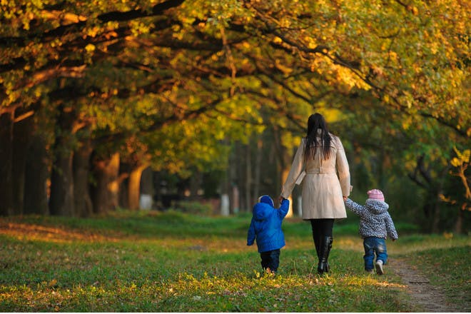 Woman and two kids walking in park