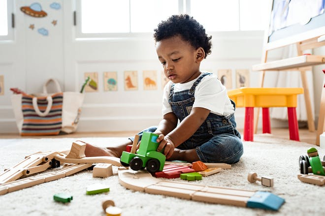 baby boy playing with wooden toys