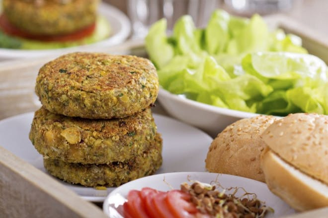 bean and carrot patties on tray with buns and lettuce