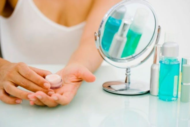 woman holding cream tub with mirror next to her