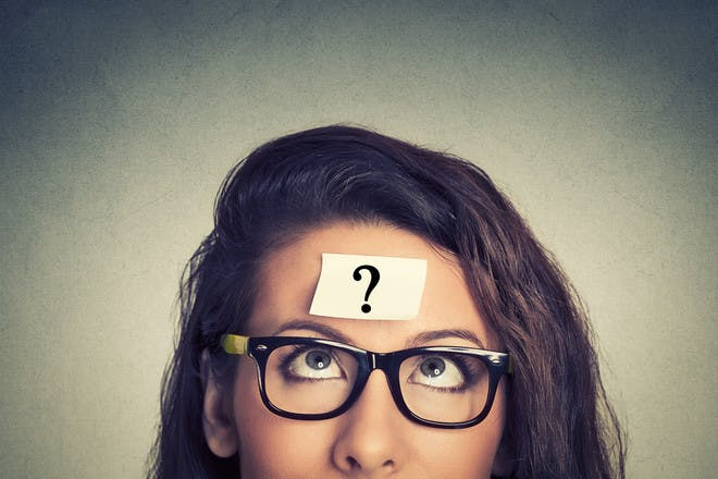 Woman with glasses and sticky note with question mark on head