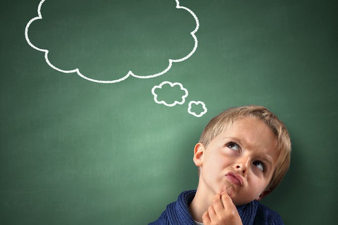 Little boy with thought bubble drawn on blackboard
