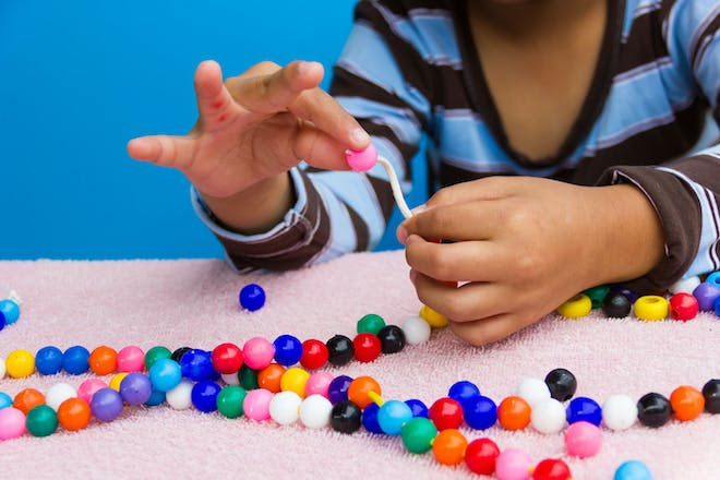 A child making jewellery with colourful beads