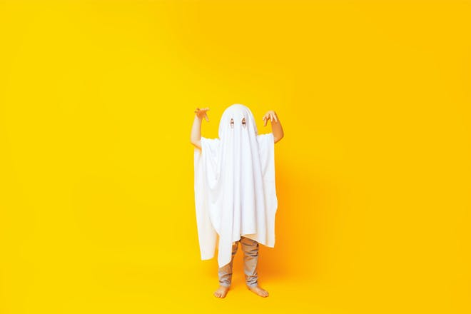 Child dressed up as ghost using white bedsheet