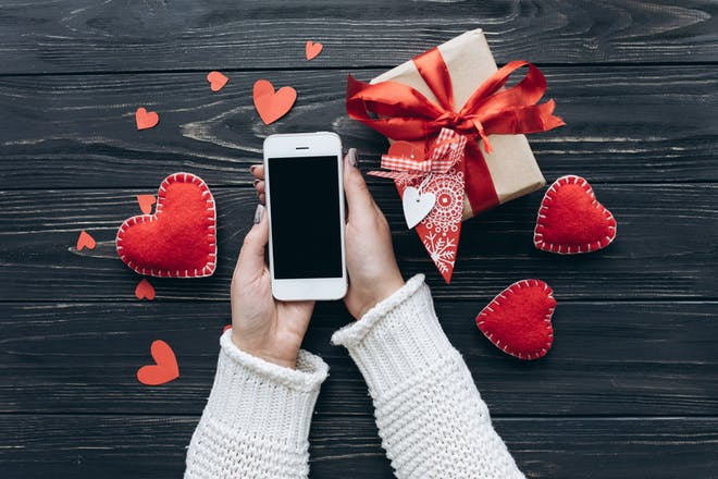 Woman with smartphone surrounded by hearts - Valentine's Day