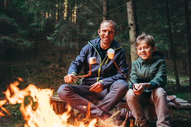 Father and son toasting marshmallows over campfire