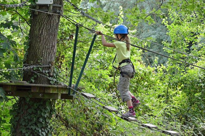 Girl crossing rope bridge at tree top adventure centre