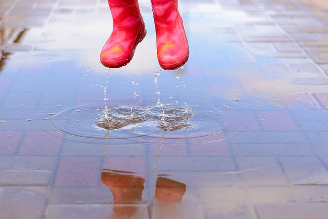 Red wellies jumping in puddle