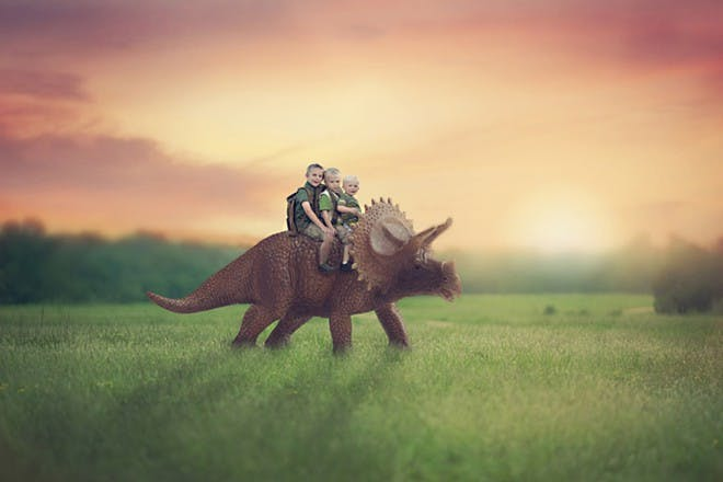 three boys riding dinosaur in field
