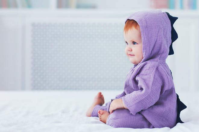 Baby with red hair wearing purple hooded dinosaur outfit