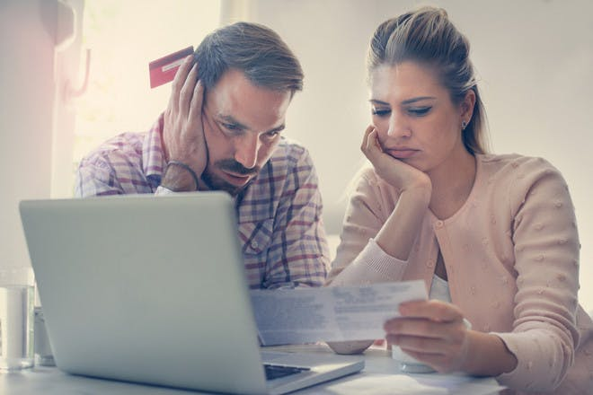 Couple looking at bills by laptop