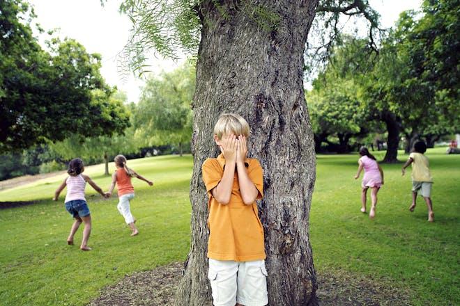 Child hides behind a tree