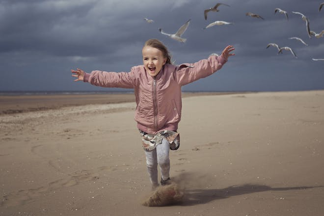Girl in pink jacket running into the wind on a beach