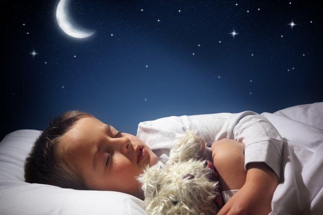 Child sleeping under night sky