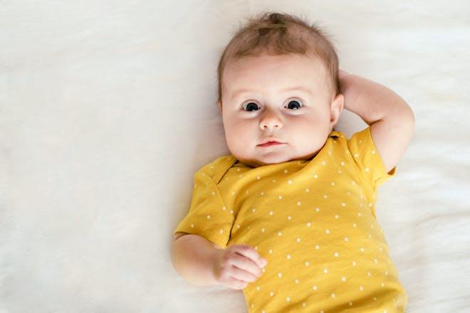 Baby lying on back wearing yellow babygro