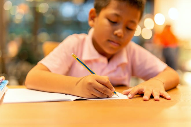 Schoolboy writing on paper at a desk