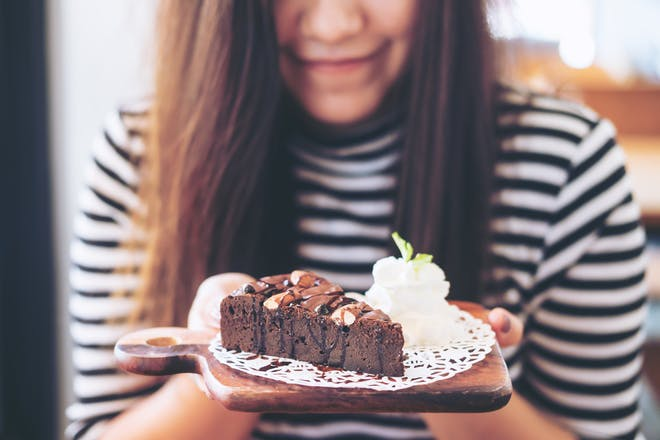woman holding plate with chocolate cake