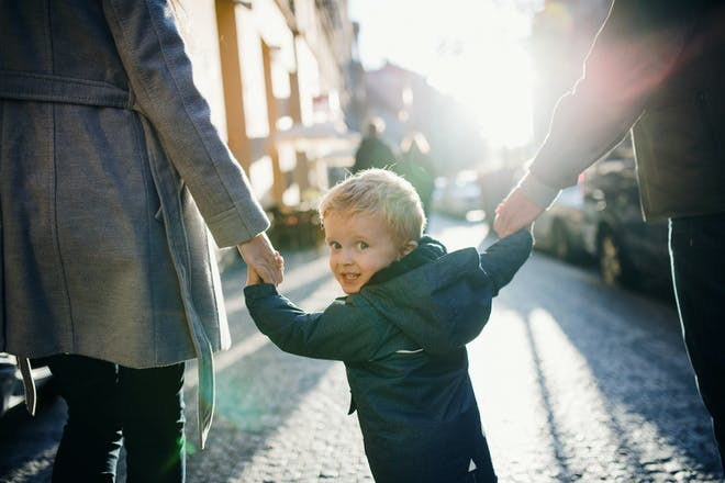 little boy holding hands with parents