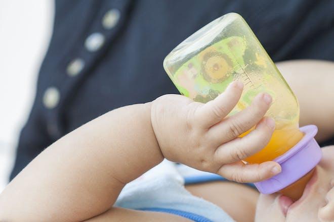 baby drinking orange juice from bottle