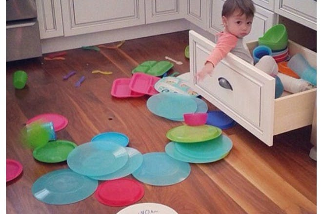 child sitting in kitchen draw pulling everything out