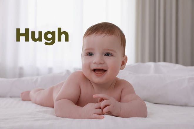 Baby lying on front on bed smiling. Name Hugh written in text