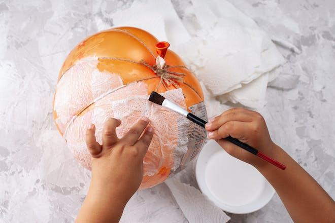A toddler's hands applying papier-mâché to a pumpkin-shaped balloon for Halloween