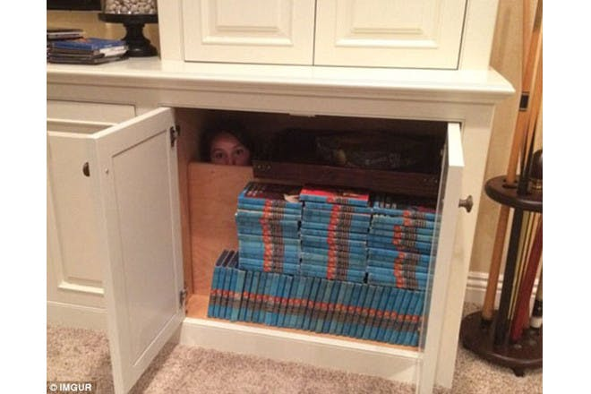child hiding behind books in cupboard