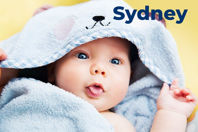 Baby wrapped in towel with tongue sticking out. Name Sydney written in text
