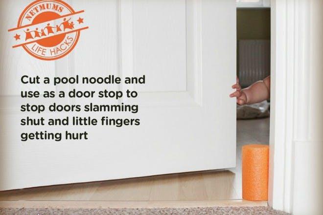 child's hand and pool noodle in door