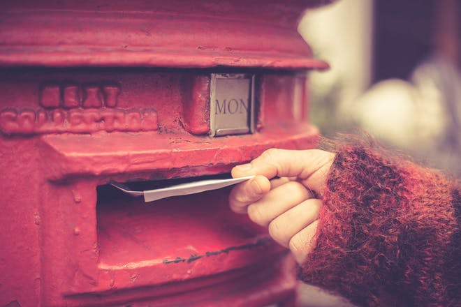 hand posting letter in red letter box