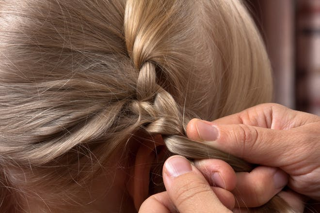 Hands doing plait in child's hair